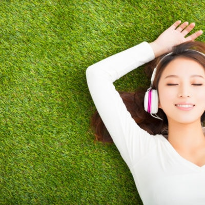Relaxed woman listening to the music with headphones lying on the grass